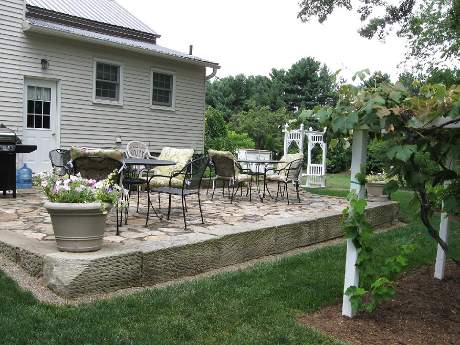 Backyard landscape featuring patio with sandstone perimeter